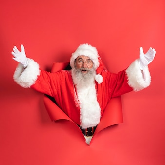 Smiley-mann im weihnachtsmannkostüm, das aus papier kommt