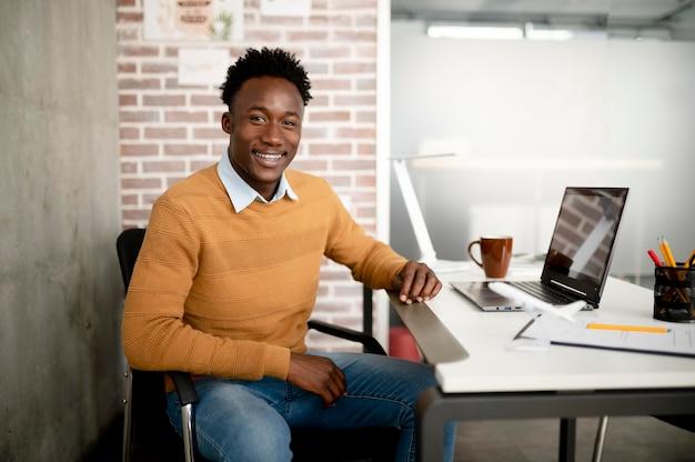 Smiley-mann mit mittlerem schuss, der am schreibtisch sitzt
