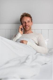 Smiley-mann mit mittlerem schuss, der am telefon telefoniert