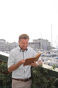 Smiley-mann mit mittlerem schuss, der ein buch liest