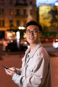 Smiley-mann mit mittlerem schuss, der smartphone hält