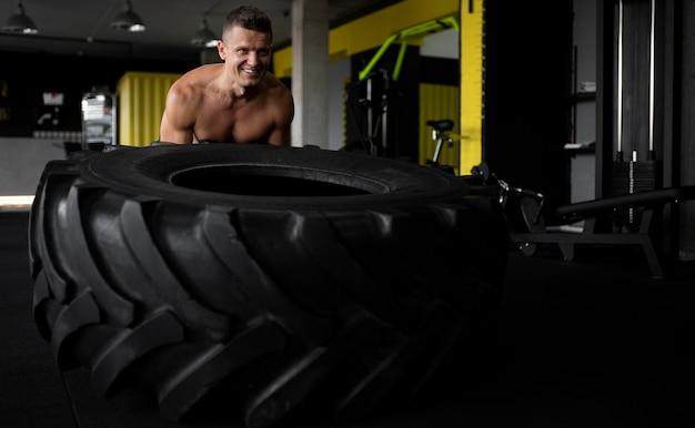 Smiley-mann mit mittlerem schuss im fitnessstudio