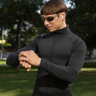 Smiley-mann mit sonnenbrille und ohrhörern, die sein fitnessband betrachten