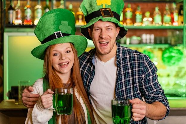 Smiley mann und frau feiern st. patricks tag an der bar