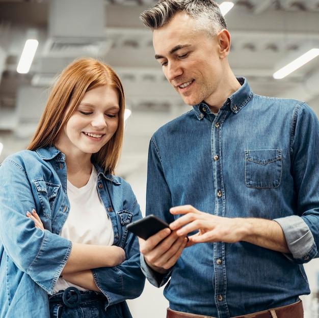 Smiley-mitarbeiter, die auf ein telefon schauen
