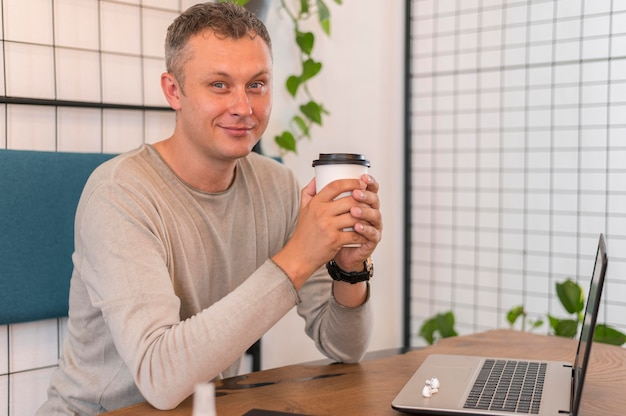 Smiley moderner mann, der eine tasse kaffee im büro hält