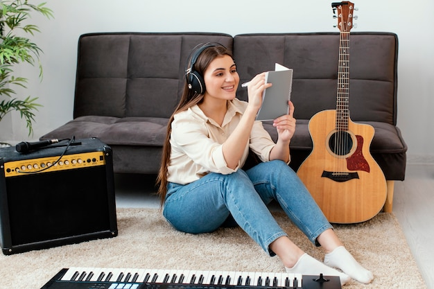 Smiley-musikerin, die neben akustikgitarre und keyboard songs auf dem notizblock schreibt