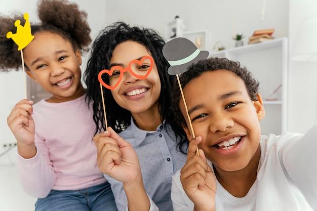 Smiley-mutter, die selfie mit ihren kindern zu hause nimmt