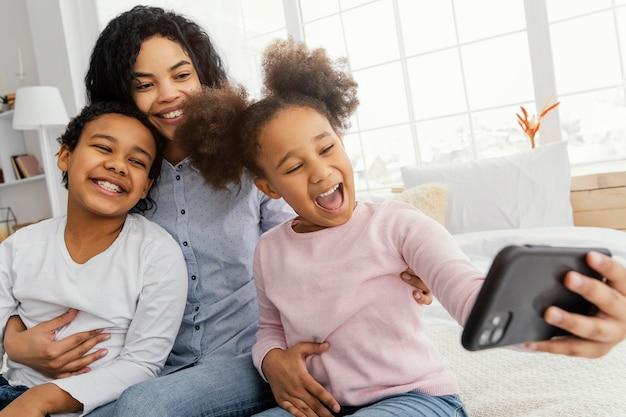 Smiley mutter und kinder nehmen selfie zu hause