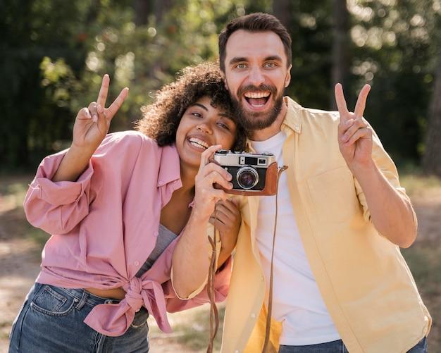 Smiley-paar, das draußen bilder mit der kamera macht