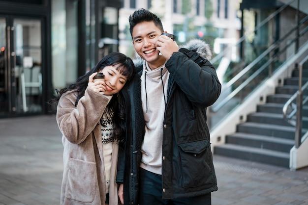 Smiley-paar, das draußen kaffee trinkt