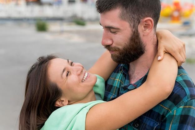 Smiley-paar, das draußen umarmt