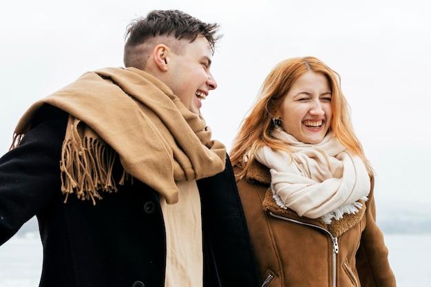 Smiley-paar, das durch den see im winter geht