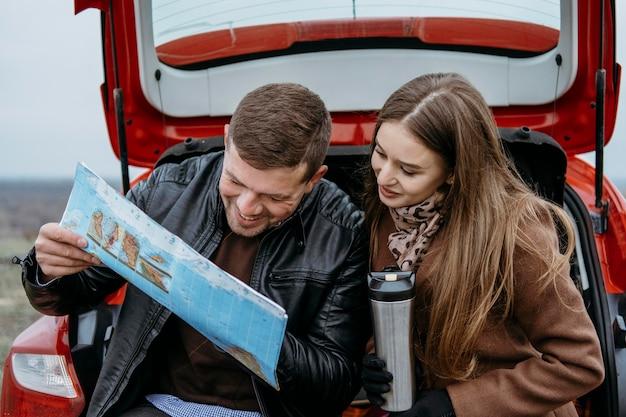 Smiley-paar, das eine karte im kofferraum des autos überprüft