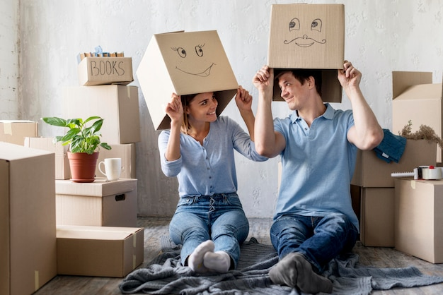 Smiley-paar zu hause am umzugstag mit kisten über den köpfen