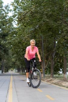 Smiley reife frau, die fahrrad draußen reitet