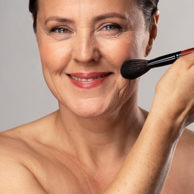 Smiley reife frau mit make-up pinsel auf ihrem gesicht