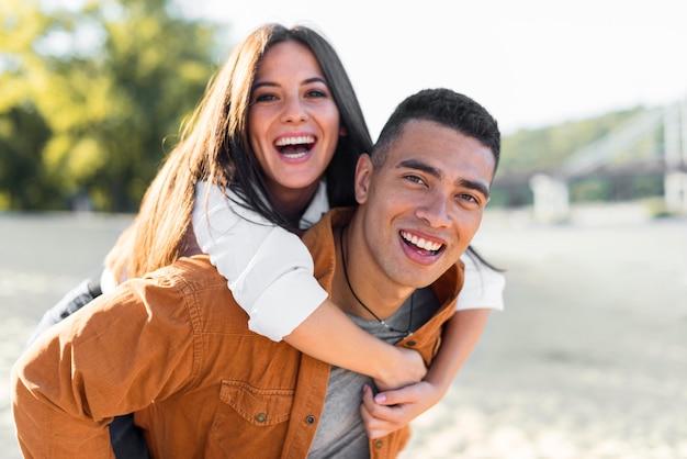Smiley romantisches paar, das zeit am strand verbringt