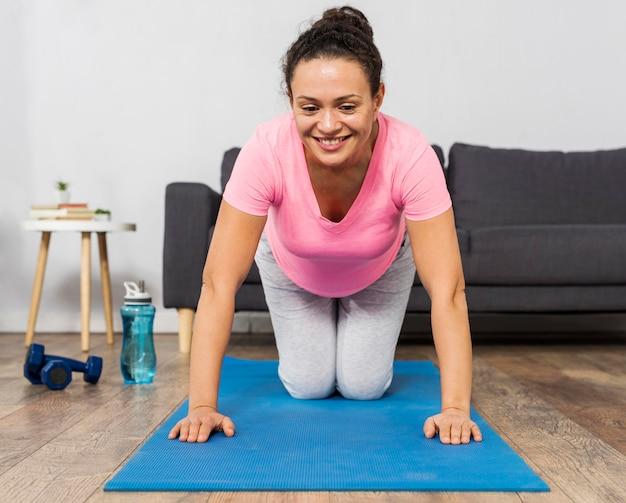 Smiley schwangere frau, die auf matte mit gewichten und wasserflasche trainiert