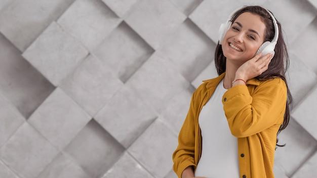 Smiley schwangere frau, die musik auf kopfhörern mit kopienraum hört
