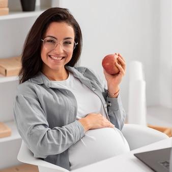 Smiley schwangere frau zu hause, die einen apfel hält