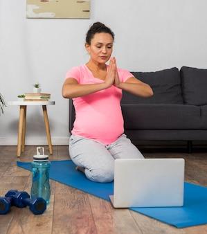 Smiley schwangere frau zu hause, die yoga mit laptop tut