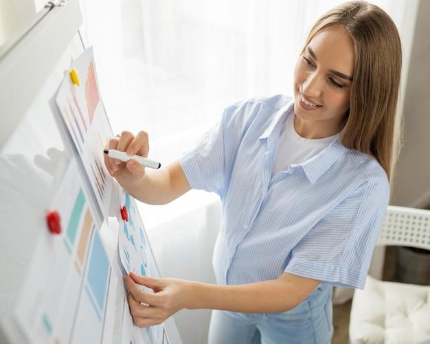 Smiley schwangere geschäftsfrau, die präsentation im büro unter verwendung des whiteboards gibt