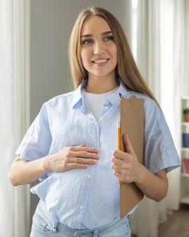 Smiley schwangere geschäftsfrau, die zwischenablage hält