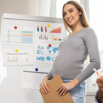 Smiley schwangere geschäftsfrau, die zwischenablage während der präsentation im büro hält