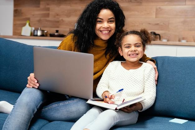 Smiley teenager-mädchen hilft kleine schwester mit online-schule auf laptop