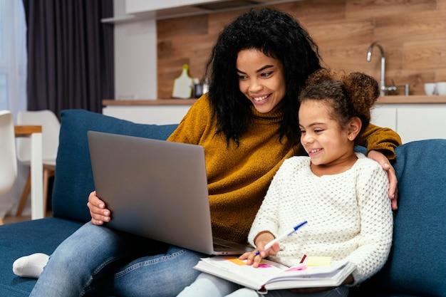 Smiley teenager-mädchen hilft kleine schwester mit online-schule