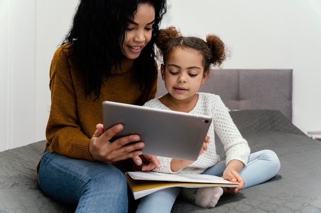 Smiley teenager-mädchen hilft kleine schwester mit tablet für online-schule