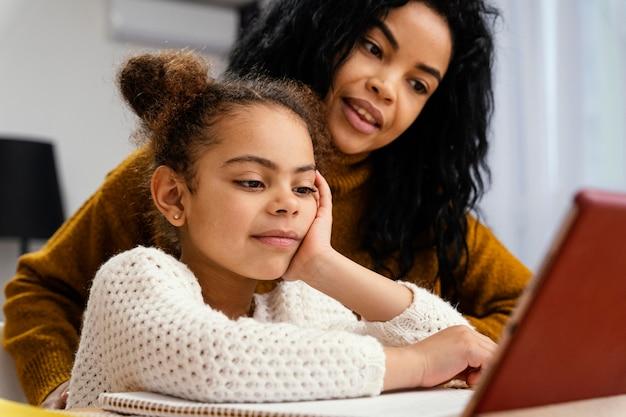 Smiley teenager-mädchen hilft kleine schwester während der online-schule mit tablet