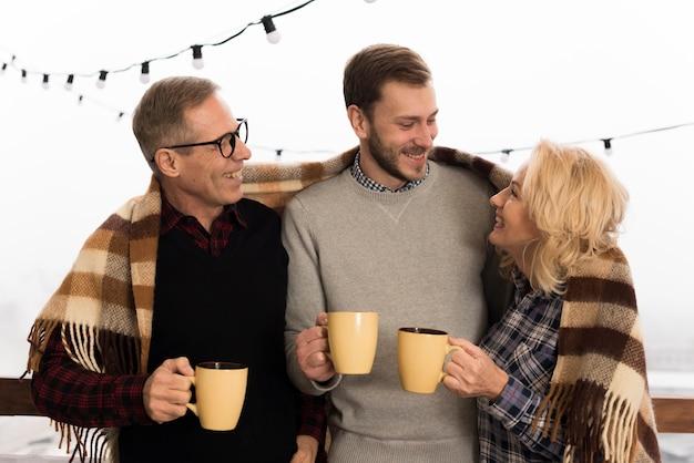 Smiley und glückliche familie, die mit schalen aufwerfen