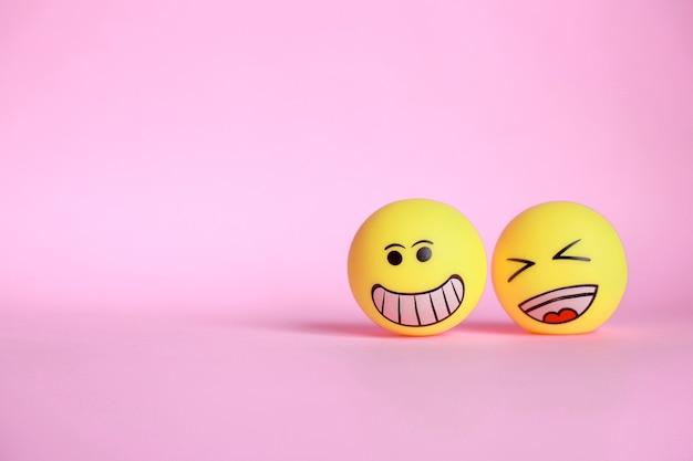 Smiley und lachen emoticon lokalisiert auf rosa hintergrund mit kopienraum