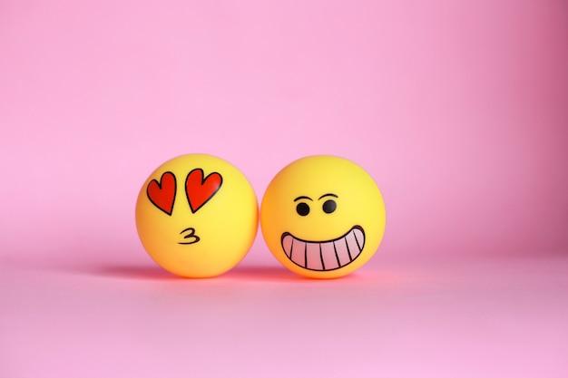 Smiley und liebesemoticon mit dem mund, der auf rosa hintergrund küsst