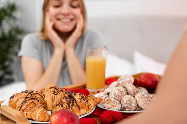 Smiley unscharfe frau, die mit frühstück im bett überrascht wird