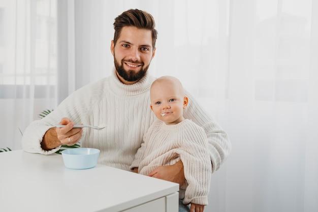 Smiley vater posiert mit baby beim füttern Premium Fotos