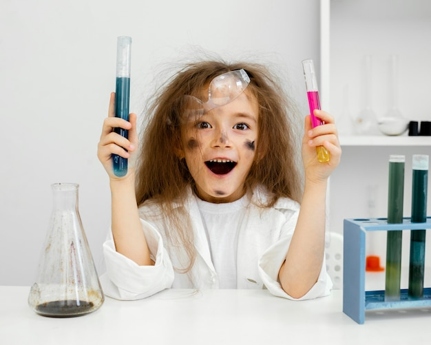 Smiley-wissenschaftlerin im labor mit reagenzgläsern und fehlgeschlagenem experiment