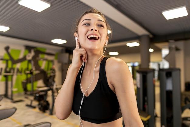 Smileyfrau des niedrigen winkels mit kopfhörern an der turnhalle