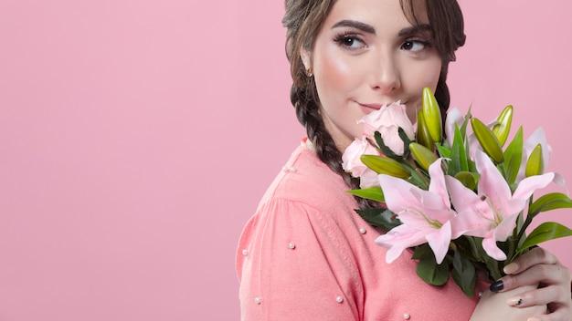 Smileyfrau, die blumenstrauß von lilien hält