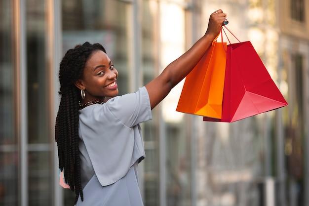 Smileyfrau, die einkaufstaschen hält