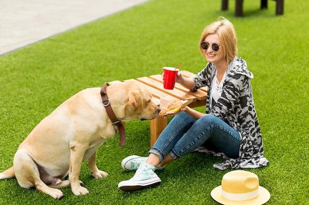 Smileyfrau, die ihrem hund lebensmittel zeigt