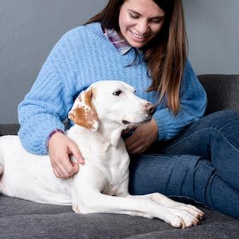 Smileyfrau, die ihren hund interessiert
