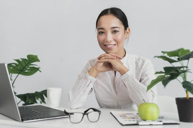 Smileyfrau, die im büro sitzt