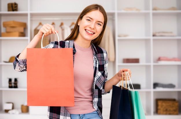 Smileyfrau, die mit den gekauften produkten glücklich ist