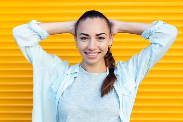 Smileyfrau, die mit gelbem hintergrund aufwirft
