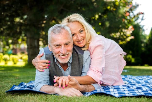 Smileyfrau, die seinen mann am picknick umarmt