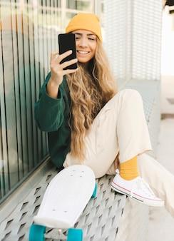 Smileyfrau, die selfie mit skateboard nimmt