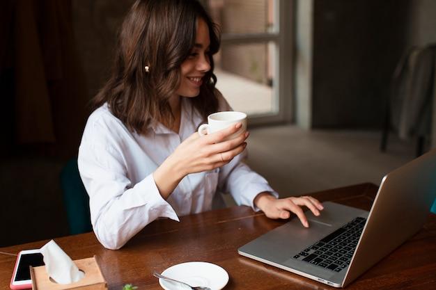 Smileyfrau, die tasse kaffee hält und an laptop arbeitet